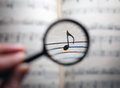 Searching for music notes through magnifying glass Stock Photography