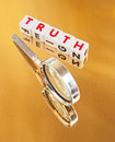 Searching for truth text in red uppercase letters inscribed on white cubes on a gold reflecting surface with a handheld silver Stock Image