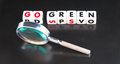 Searching for ways to go green text in upper case letters on white cubes with hand magnifier dark background Stock Photos