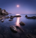 Seascape with moon and lunar path with rocks at night Royalty Free Stock Photo