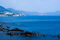 Seascape and the official flag of genova italy a beautiful mountain view in background a with rocks town in front Stock Image
