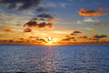Seascape sunset sun setting over calm seas Royalty Free Stock Image