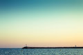 Seascape view with blue to orange sky gradient at sunset and pier at the horizon copy space Royalty Free Stock Photos