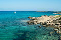 Seashore of cyprus island with rocky coast and white yacht in mediterranean sea Royalty Free Stock Images