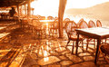 Seaside cafe in sunset light bright orange cute bar with wooden chairs and tables on sea shore luxury resort summer vacation Stock Photos