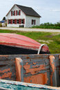 Seaside cottage in maine by the sea with rowboats with peeling paint in the foreground Stock Photography