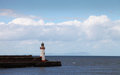 Seaside lighthouse on a harbor jetty Royalty Free Stock Images