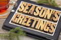 Season greetings typography s text in letterpress wood type on a digital tablet with a cup of tea Royalty Free Stock Photography