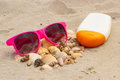 Seasonal concept heap of shells sunglasses and sun lotion pink on sand at the beach protection from Royalty Free Stock Photos