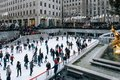 Seasonal ice skating rink with a golden statue, in a famed complex with upscale shops & restaurants in Rockefeller Center Midtown Royalty Free Stock Photo