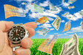 Seasonal summer financial performance collage with currency and a clock in a hand on a background of sky and grass Royalty Free Stock Image