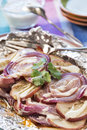 Seasoned red potatoes and onions grilled with bacon were in a foil packet drizzled ranch dressing Royalty Free Stock Images