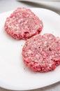 Seasoning raw burger on white plate Royalty Free Stock Photography