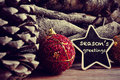 Seasons greetings the text written in a star shaped blackboard and some christmas balls pinecones and a pile of logs in the Stock Photo