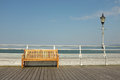 Seat and light a wooden on a boardwalk against a silver painted railing with a on a post against the sea sky Royalty Free Stock Photography