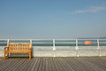 Seat s o s a wooden on a boardwalk against a silver painted railing with an orange sign with the letters with the sea and sky in Stock Photography