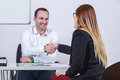 Seated businessmen and businesswoman shaking hands in office Royalty Free Stock Photography