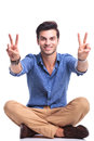 Seated casual man making the victory sign and smiles Royalty Free Stock Photo