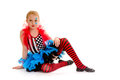 Seated child circus jester in colorful costumer dancer poses costume as a painted Stock Image