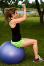 Seated dumbbell fly young woman on an exercise ball doing the Royalty Free Stock Photos