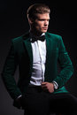 Seated elegant man in green velvet suit side view of a he looks away from the camera on black background Royalty Free Stock Photo
