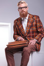 Seated fashion man with long beard and briefcase looking at the camera Royalty Free Stock Photo
