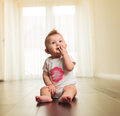 Seated little girl chewing on her fingers and looks up Royalty Free Stock Photo