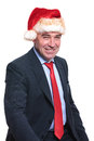 Seated old business man wearing a christmas hat is smiling to the camera Royalty Free Stock Photo