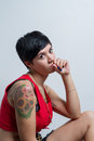 A seated short-hair brunette woman wearing a red tank top lookin Royalty Free Stock Photo