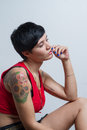 A seated short-hair brunette woman wearing a red tank top Royalty Free Stock Photo