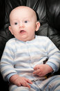 Seated talking baby chubby boy with blue eyes and surprised expression on his face sitting up Stock Images