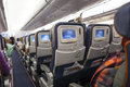 Seating space with multimedia screens economy class airplane cabin Royalty Free Stock Photo