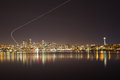 Seattle skyline by night with airplane trail an Stock Image