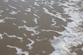 Seaview waves with whitecaps flood the sandy beach Stock Photos
