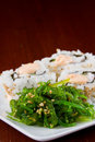 Seaweed salad and sushi closeup with rolls in the background served on a white plate Stock Photo