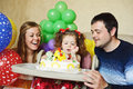 Second birthday toddler girl and her parents sitting with cake Royalty Free Stock Photos