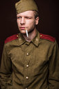 Second world war russian soldier smoking cigarette and looks at something studio portrait isolated on brown background Royalty Free Stock Image