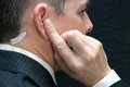 Secret service agent listens to earpiece close side up of a listening his Stock Photos