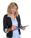Secretary with blue blazer and clipboard writing note on an isolated white background for cut out Royalty Free Stock Images