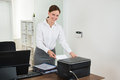 Secretary inserting paper in printer young female at desk Royalty Free Stock Image