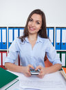 Secretary with long dark hair and calculator at office Royalty Free Stock Photo