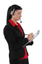 Secretary wearing headset and taking notes Stock Photos