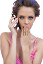 Secretive model wearing hair rollers with phone young on the against white background Royalty Free Stock Images