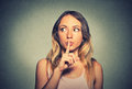 Secretive woman placing finger on lips asking shh, quiet Royalty Free Stock Photo