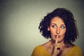 Secretive woman placing finger on lips asking shh quiet silence looking sideway closeup portrait young gray background human face Royalty Free Stock Photos