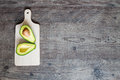 Sectioned fruit avocado on a chopping board with place for a text Royalty Free Stock Photo