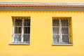 Secured windows of an yellow building Stock Image