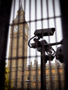 Security camera monitoring area behind bars metal fence around big ben houses parliament Royalty Free Stock Photos