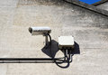 Security camera wall mounted in urban setting on stone with power box and cables Stock Image