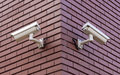 Security cameras two on the brick wall overlooking opposite sides Royalty Free Stock Photography
